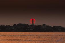 Le soleil se couche dans le phare de l'ile de Batz, sa lueur rouge innonde l'océan