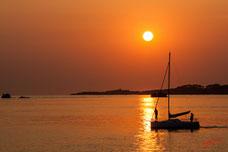 Voilier au départ, devant le soleil couchant, lumiere orangée de la bretagne