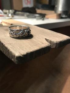 Une bague irrégulière est posée sur la cheville de l'établi du bijoutier.