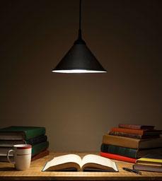 Foto von Bücher am Tisch, beleuchtet von einer Hängelampe