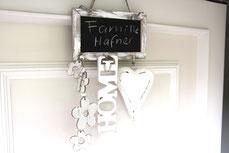 Kreidetafel mit Deko an weißer Haustür.