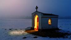 Une petite chapelle isolée la nuit dans laquelle brille une si forte lumière qu'elle éclaire l'extérieur