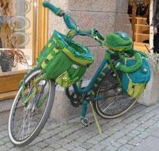 Ein Fahrrad mit Fahrradkorb und Fahrradtasche am Gepäcksträger ist vollständig mit einem gestrickten Mantel umhüllt.
