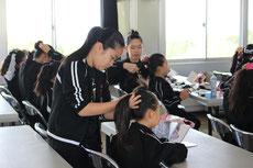 髪型の練習では、お姉さんたちが小さい子たちに指導をします。