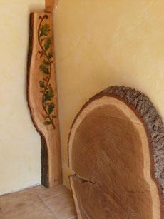 Eichenscheibe Durchmesser ca. 1m, dahinter Säule aus Eiche mit Rankenornament und Baumkante
