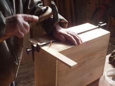 新しく作った前板を本体と接合修理をしています。木釘を打っています。