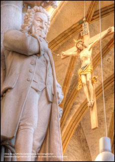 Es ist eine Innenaufnahme im Ulmer Münster. Man sieht vorne links das Denkmal von JS Bach, rechts im Hintergrund ist ein Kreuz, an dem Jesus angenagelt hängt. Es sind braun-beige Farbtöne.