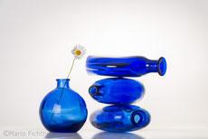 Blaue Flaschen vor weißem Hintegrund im Studio mit Blume