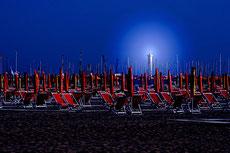 Liegestühle am abendlichen Strand vor Leuchtturm