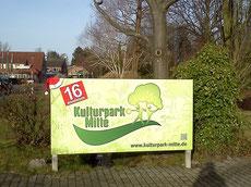 """Mit Weihnachtsmützen und einer großen """"16"""" verzierte Hinweisschilder des Kulturparks"""