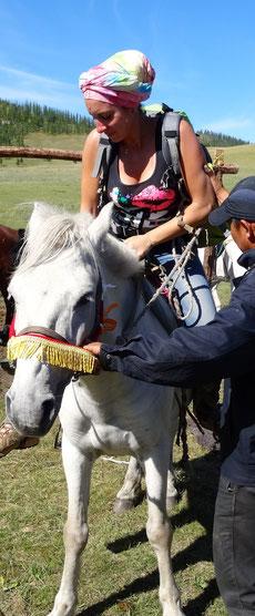 La montée en selle avec l'aide du guide mongol