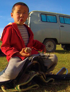 Enfant mongol en selle s'amuse à coté du 4X4