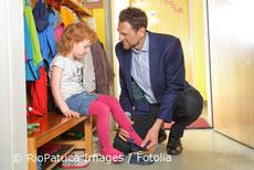 Foto - Junger Vater zieht seiner Tochter den Schuh an