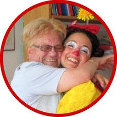 Alter Mensch umarmt therapeutischen Clown Angelina Haug