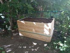 Man sieht ein einzelnes Hochbeet im Garten, das gerade angelegt wurde.
