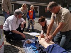 Passanten üben die Herz-Lungen-Wiederbelebung mit Hilfe eines Defibrillators.