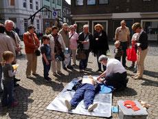 Michael Görlich von den Düsseldorfer Maltesern zeigt vor der Basilika, wie die Defibrillatoren benutzt werden.