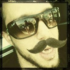 Mann mit Bart u Sonnenbrille. Es soll erraten werden, welches Bandenmitglied es ist.