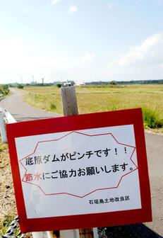 ほ場の近くに設置された節水を呼び掛ける看板=20日午後、石垣市新川