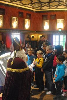Der kniende Nikolaus übergibt einem kleinen Jungen einen echten Schokonikolaus.