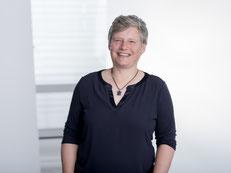 Portraitbild von Antje Friedrichsen, lachende Frau mit kurzen, grauen Haaren