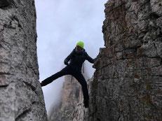 Ganzkörperbild von Dr. Liana Matern, kletternde Frau in Felsspalte in den Alpen