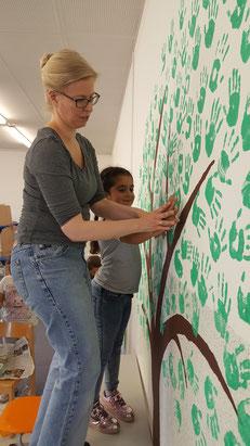 Frau Ernst hilft Dilara bei ihrem Handabdruck