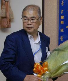 受賞祝いの花束を持つ高橋保一氏