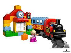 Im Paket Lego 10507 Eisenbahn Starter Set sind 52 Einzelteile, eine Dampflok, ein Lokführer, eine Kinderfigur, ein Passagierwaggon, eine Tankpumpe, ein Signal, eine Ziege, eine Blume, ein Koffer und diverse DUPLO Steine und jede Menge Schienenelemente ent