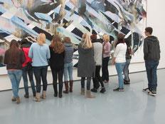 Besuchergruppe steht vor einem Gemälde