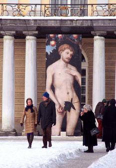 Menschen gehen im Schnee vor Riesenplakat mit Nacktem Mann, Ausstellung im Neuen Flügel Schloss Charlottenburg. Foto: Helga Karl