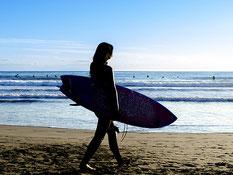 湘南の海でサーフィンをする女性