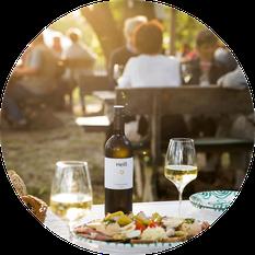 Heurigenjause, Gebäckskorb und Wein im Gastgarten des Weingut Heiß sind angerichtet.
