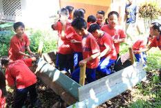家から持ち寄った野菜くずや鶏糞と、落ち葉を混ぜてたい肥づくりをする子どもたち