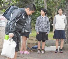 校門前の線で止まってあいさつする児童。写真右は嵩原さん=6日、宮良小学校