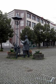 """Marktplatz von Dudweiler mit Denkmal """"Monn mit da long Stong"""" von Zoltan Hencze"""