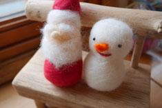 サンタさんにおひげとまゆ毛をつけます。白い羊毛をニードルという針でチクチク刺していきます。雪だるまのお顔をつけます。