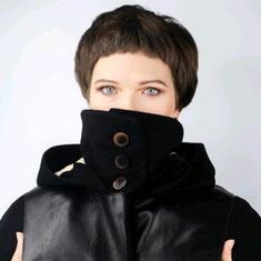 Braunhaarige Frau trägt eine schwarze Jacke mit Ledertaschen und Kapuze. Mund und Nase sind verdeckt