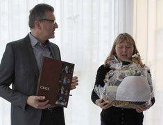 Claus Hulin erhält von Constanze Schürer stellvertretend für das gesamte Kollegium einen von vielen Abschiedsgrüßen.