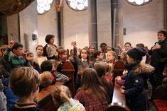 """""""Warum sind die vier Evangelisten mit einer Feder auf der Kanzel dargestellt?"""", fragt Emma (mit Feder)  die Kinder. (Foto: A. Fröhling)"""