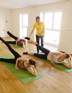 Pilates-Kursstunde in der Gruppe - Trainer korrigiert Haltung