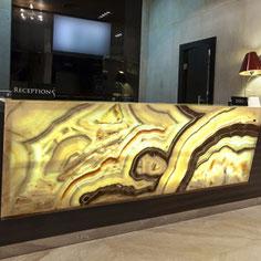 Registratūra viešbučio hole iš šviesai laidaus natūralaus onikso - meno kūrinys