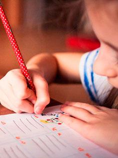 Kind lernt mit der Hand leserlich zu schreiben