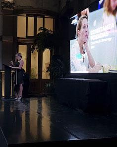 chica en un discurso colocada frente a una pantalla led KLS