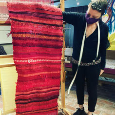 Frau präsentiert stolz fertigen roten Flickenteppich