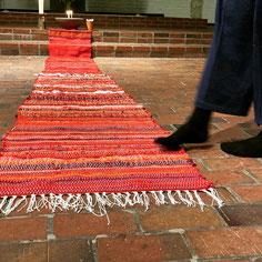 Fuß berührt sehr langen Roten Flickenteppich auf dem Kirchenboden