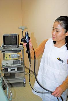 石垣市の胃検診で使われる胃カメラを持つ職員。左のモニターも古い機種になっている=16日午後、市健康福祉センター