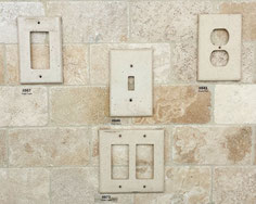 A travertine backsplash with travertine-colored outlet cover.