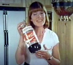Pub jeune femme souriante arborant une bouteille en plastique Coca Cola