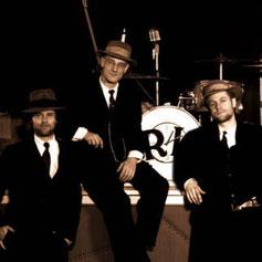 Die drei Musiker in Anzügen sitzend vor der Bühne